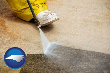 pressure washing a concrete surface - with North Carolina icon