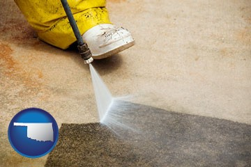 pressure washing a concrete surface - with Oklahoma icon